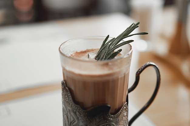 Une tasse de chocolat chaud avec une branche de romarin dans un porte-gobelet en métal vintage.