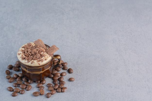 Tasse de chocolat chaud et grains de café sur pierre.