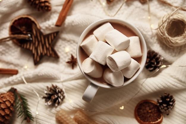 Tasse de chocolat chaud avec une guimauve et des décorations de noël.