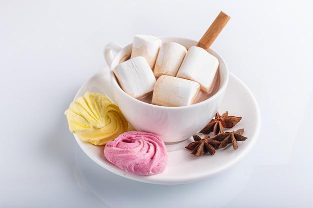 Une tasse de chocolat chaud avec guimauve, meringue et épices isolés sur blanc.