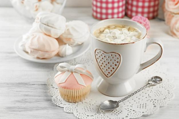 Tasse de chocolat chaud avec des guimauves, sur fond de bois clair