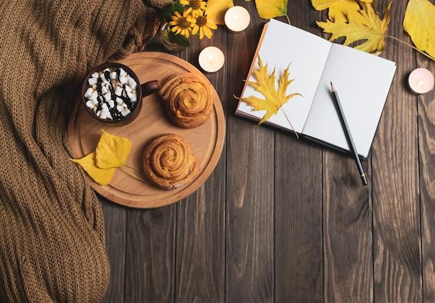 Tasse de chocolat chaud avec des guimauves sur un plateau en bois.