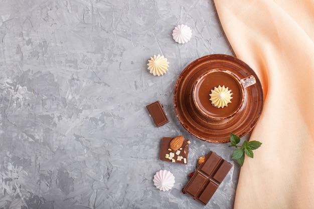 Tasse de chocolat chaud et morceaux de chocolat au lait aux amandes