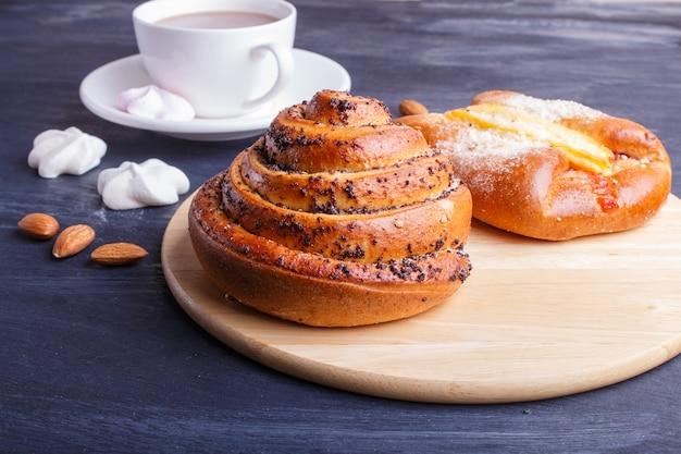 Une tasse de chocolat chaud et de petits pains sur une surface en bois noire.