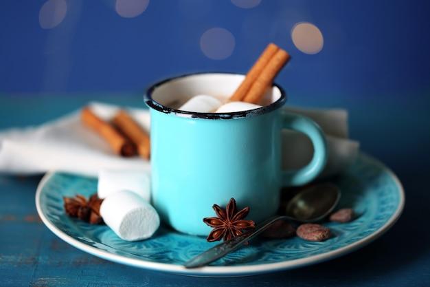 Tasse de chocolat chaud savoureux, sur table en bois, sur fond brillant