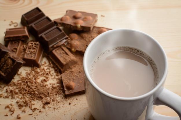 Tasse de chocolat chaud avec de la vapeur près de différentes barres de chocolat cassées avec des noisettes sur table