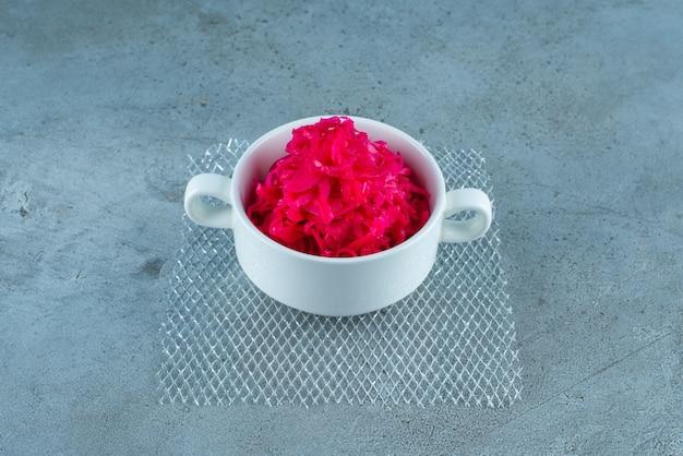Une tasse de choucroute fermentée rouge, sur la table bleue.