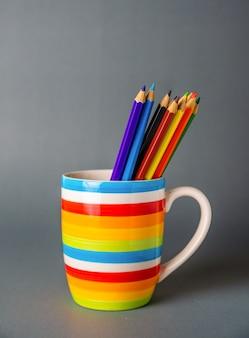 Une tasse colorée aux crayons sur fond gris