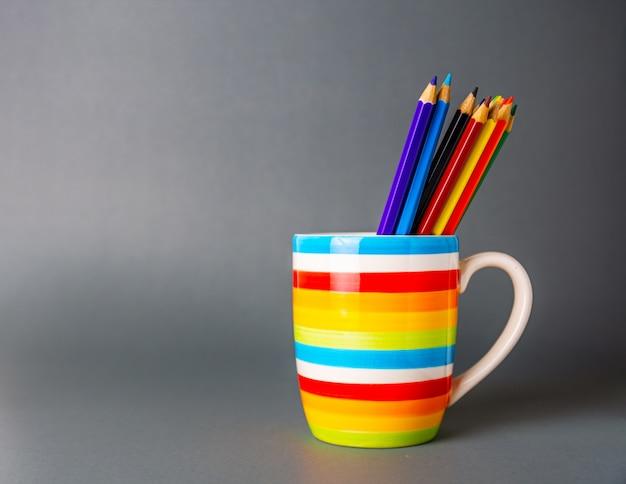 Une tasse colorée avec un groupe de crayons de toutes les couleurs en gris