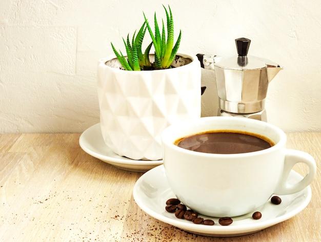 Tasse de couleur blanche de café noir avec soucoupe et haricots, cafetière en aluminium, plante succulente verte en pot blanc sur table en bois beige. mise au point sélective. copier l'espace