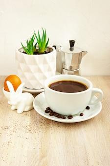 Tasse de couleur blanche de café noir avec soucoupe et haricots, cafetière en aluminium, plante succulente verte en pot blanc sur table en bois beige. porte-oeuf de lapin de pâques. mise au point sélective. copier l'espace