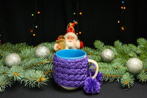 Une tasse avec une couverture en laine tricotée sur fond de branches de sapin du nouvel an.