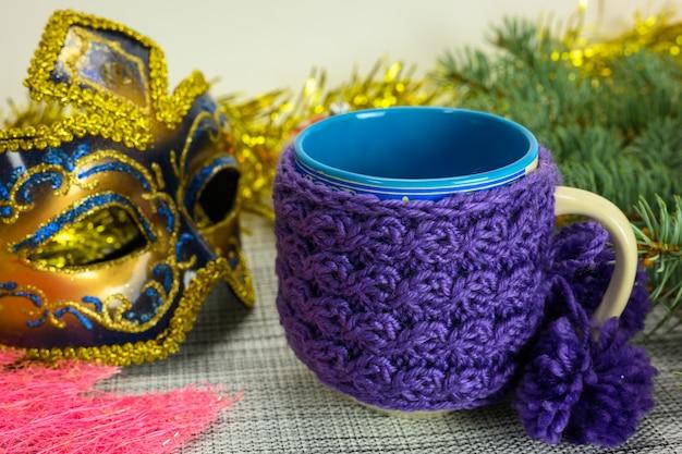 Une tasse avec une couverture tricotée sur fond de branches d'arbres de noël.