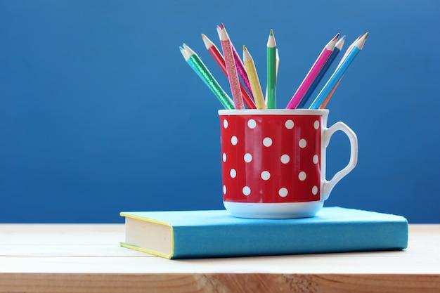 Tasse avec des crayons de couleur et livre sur une table en bois sur un fond bleu.