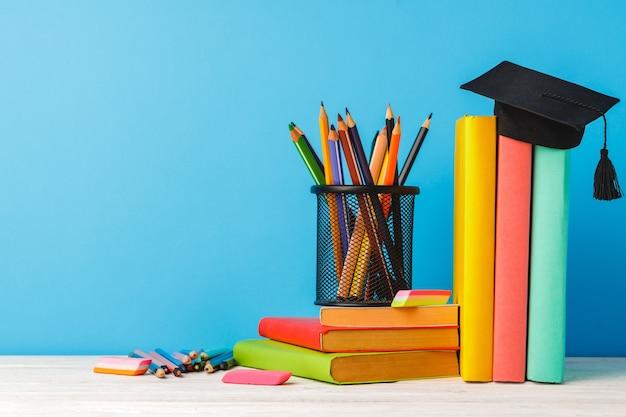 Tasse de crayons de couleur et pile de livres sur table