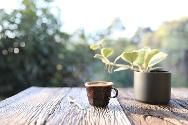 Tasse et cuillère à café brunes en argile avec plante hoya