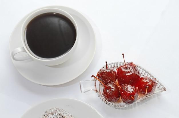 Tasse avec cuillère, confiture de pommes dans un bol. fond blanc.