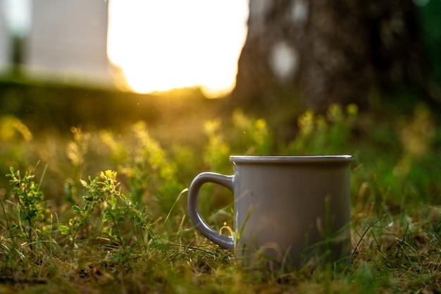 Une tasse dans l'herbe le concept d'écologie et de tourisme