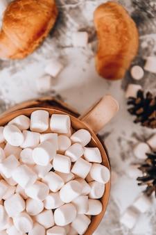 Une tasse de délicieux chocolat chaud de noël nouvel an et cacao avec des guimauves saupoudrées de cacao...