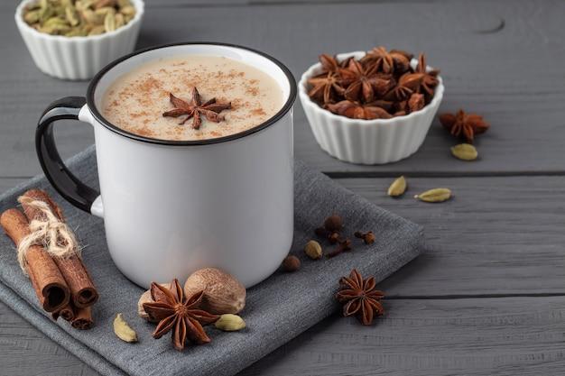 Tasse avec délicieux thé masala indien et condiments sur table en bois gris