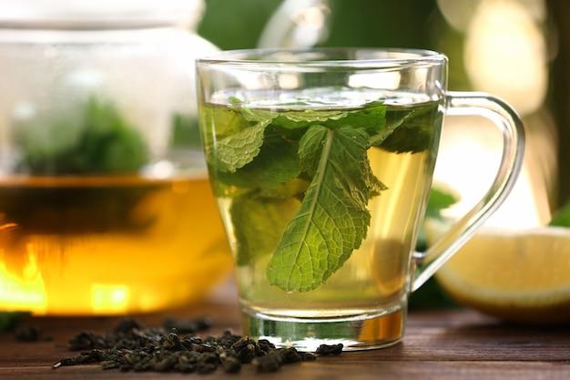 Tasse avec un délicieux thé à la menthe sur table, gros plan