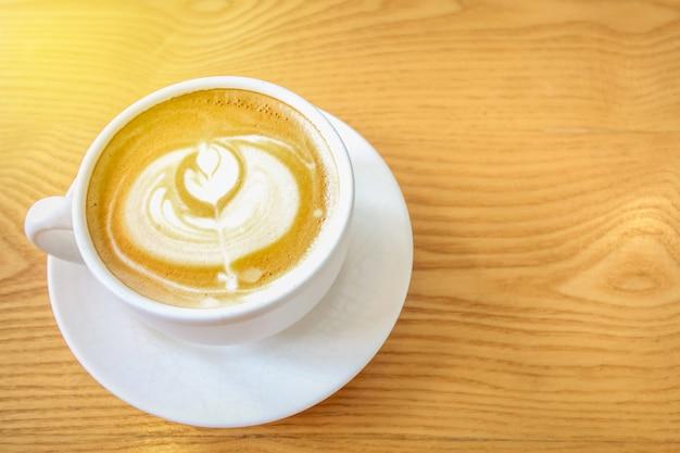 Tasse du café latte art avec cuillère et assiette
