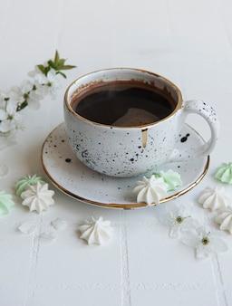Tasse avec du café et de petites meringues sur une surface carrelée