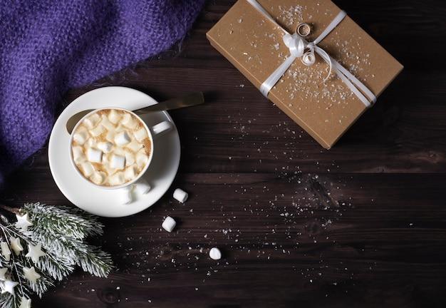 Une tasse avec du chocolat chaud et des guimauves, une couverture tricotée, sur un fond en bois sombre.