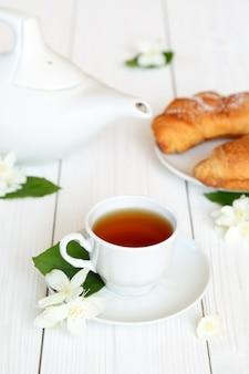 Tasse avec du thé au jasmin et des fleurs de jasmin sur un fond en bois clair