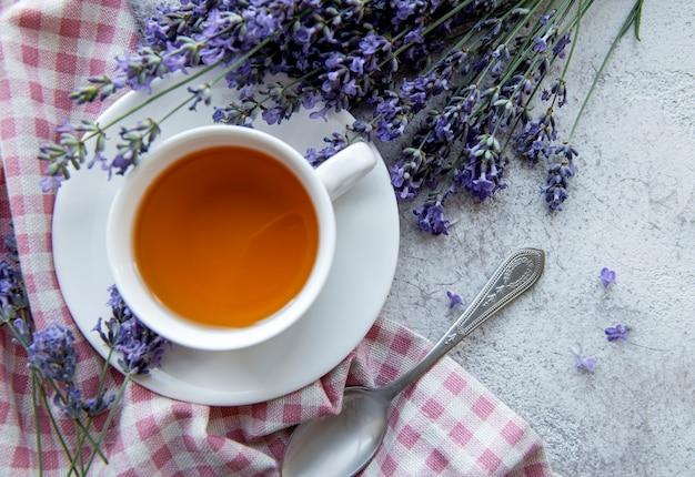Tasse avec du thé à la lavande et des fleurs de lavande fraîches
