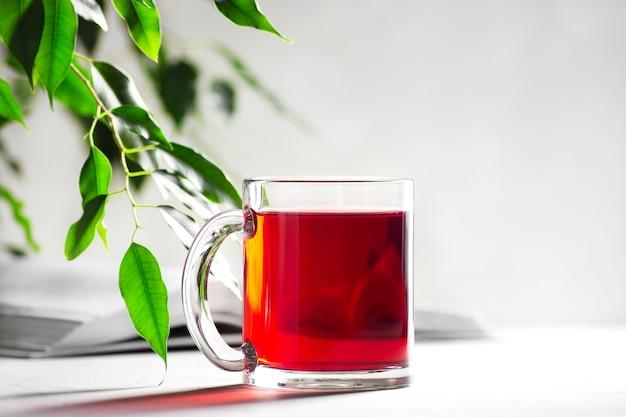 Une tasse avec du thé rouge sur fond gris clair, un livre se trouve à côté
