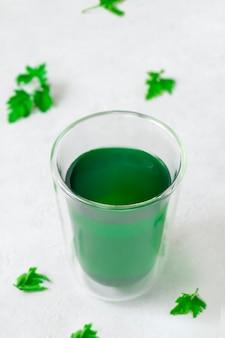Tasse avec de l'eau de chlorophylle sur fond gris neutre avec des feuilles vertes image verticale