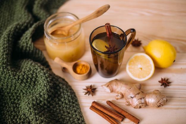 Tasse d'eau tiède avec du citron, du miel, du gingembre, de la cannelle et de l'anis.