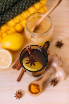 Tasse d'eau tiède avec du citron, du miel, de la racine de gingembre, de la cannelle et de l'anis.