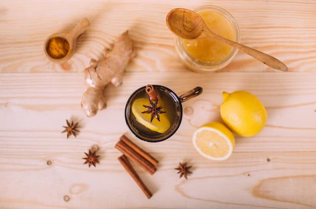 Tasse d'eau tiède avec du citron, du miel et de la racine de gingembre.