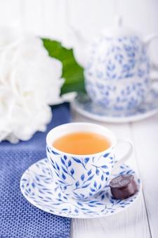 Tasse élégante de thé vert, bonbons et fleur d'hortensia blanc
