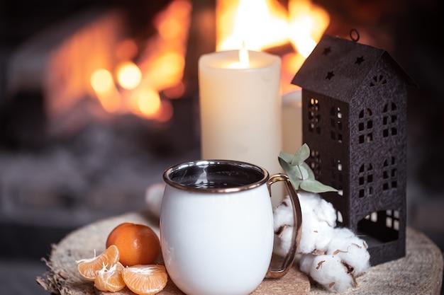 Une tasse avec des éléments décoratifs sur une souche en bois près de la cheminée. le concept d'un village vacances en dehors de la ville.