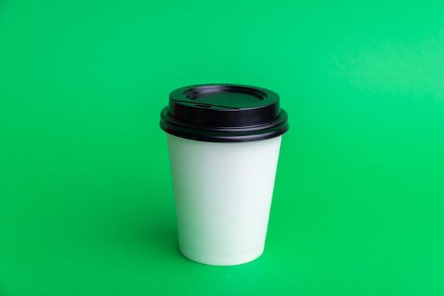Une tasse à emporter blanche avec capuchon noir sur fond vert