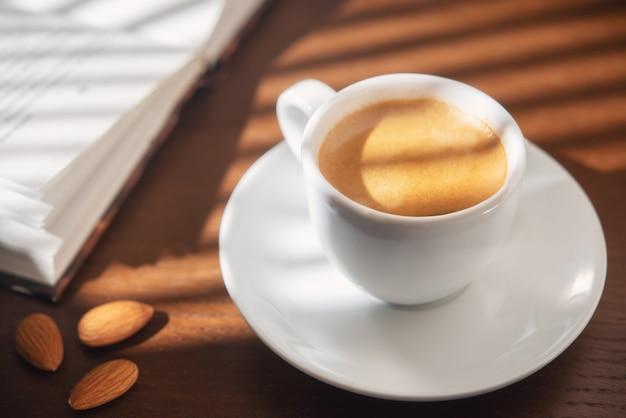 Une tasse d'espresso aux amandes et un livre dans la lumière du matin