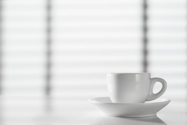Tasse d'espresso blanc sur la table contre la fenêtre