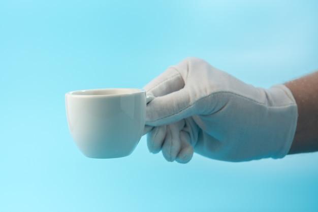 Tasse d'espresso à la main avec gant