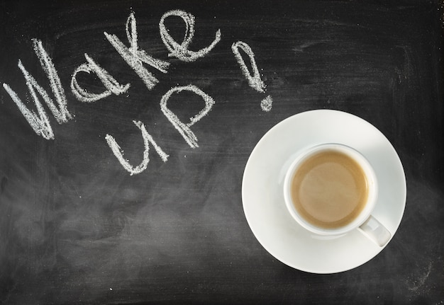 Une tasse d'expresso sur un tableau noir. réveillez-vous!