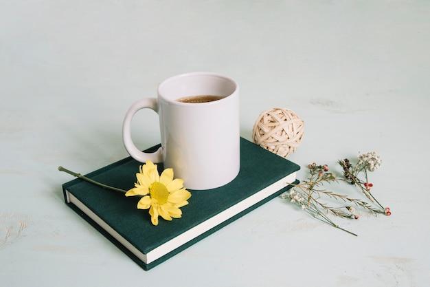Tasse et fleur sur cahier