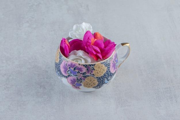 Une tasse de fleurs violettes et blanches, sur le tableau blanc.