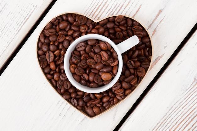 Tasse et forme en forme de cœur remplies de grains de café. vue de dessus à plat. bois blanc en surface.