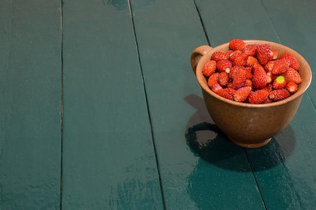 Une tasse de fraises se dresse sur une table verte en bois à droite