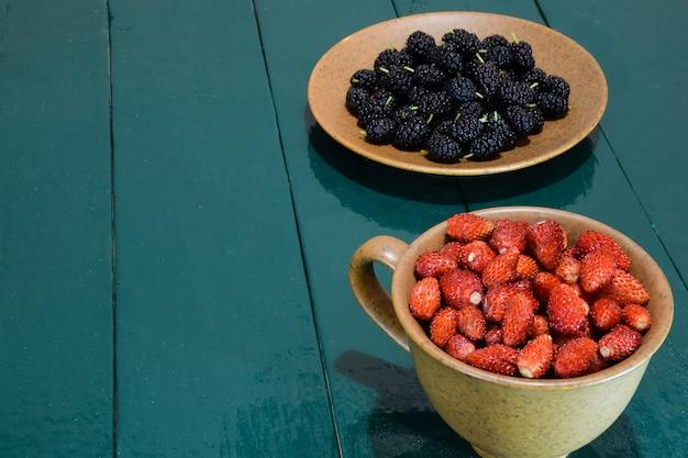 Tasse avec fraises et soucoupe avec mûres se tiennent sur une table verte en bois