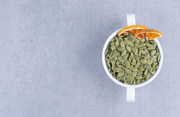 Une tasse de graines de citrouille savoureuses avec du citron séché sur du marbre.