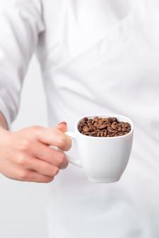 Tasse de grains de café en main féminine