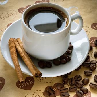 Une tasse de grains de café naturels et de cannelle